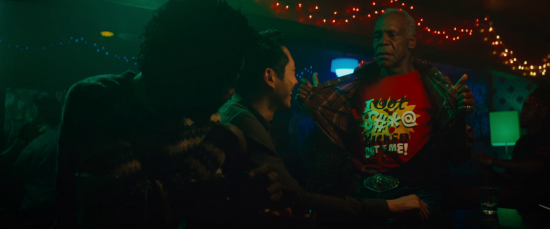 In a dark pub, Lakeith Stanfield and Steven Yeun sit at the bar facing right, where Danny Glover stands up beside them holding his shirt open to reveal a red T-shirt with the text 'I got the s#*@ kicked out of me!'