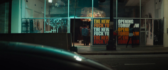 View of the front of a city venue at night from across the street. Two characters stand talking just inside the open door, and the rest of the facade is all large rectangular panes of glass. One window has a poster saying 'Opening Tomorrow' three times, in white, yellow, and orange. The window beside it says 'The New Fuck You' in the same colours.