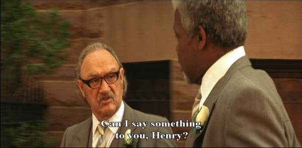 "Royal (Gene Hackman) and Henry (Danny Glover) are walking and talking, right to left, close up. Both are wearing smart grey suits and white shirts. Royal wears black-rimmed glasses. Royal says: ""Can I say something to you, Henry?"""