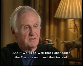 "John Boorman speaks to interviewer, with caption saying: ""And it works to well that I abandoned the F-words and used that instead."" He faces slightly right and wears a dark collarless jacket over blue T-shirt. A beige lamp is lit behind him, in front of closed curtains."